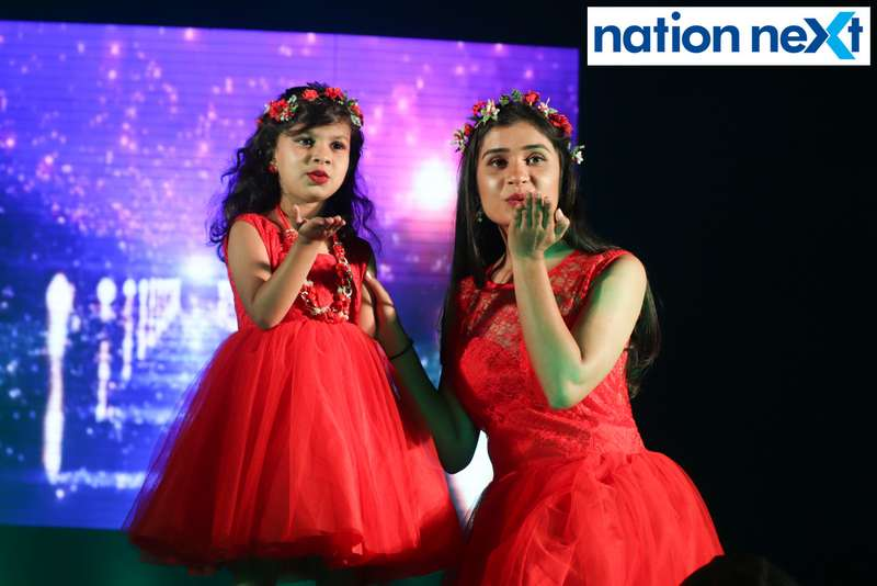 A model poses for a picture with a little girl during IFT Fashion Carnival held in Nagpur