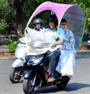 Nagpurians beat the heat: Nagpur couple is seen riding a bike with an attached motorcycle umbrella as protection against intense heat wave.