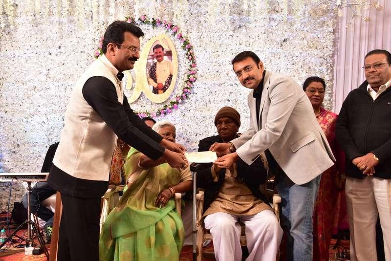 Sanjay Gupta (left) and Nagpur Mayor Sandip Joshi giving away a donation cheque to an elderly couple during Gupta's 50th birthday celebration in Nagpur
