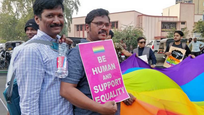 A man carries a placard supporting LGBTQI community during Orange City Pride March in Nagpur