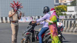 Police Inspector Rajesh Babu speaks to commuters while wearing 'Coronavirus helmet'